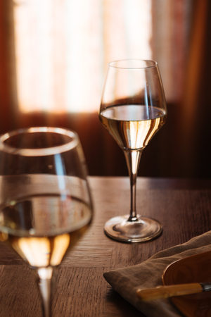 Two glasses of Traminer on a wooden table in a restaurant. Traminer is an italian aromatic wine grape variety used in white wines, that performs best in cooler climates.