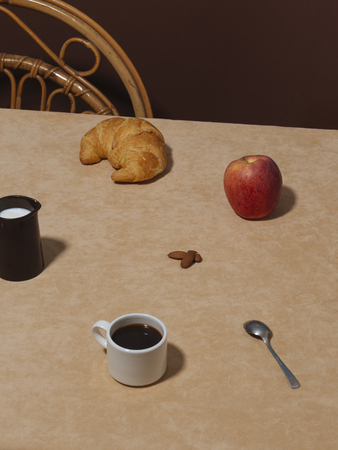 A table ready for breakfast, with italian espresso coffee, apple, almonds, milk and a croissant