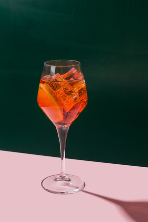 Venetian Spritz, an IBA cocktail with Prosecco or white sparkling wine, bitters, soda, ice and a slice of orange, in a calix on a table, pop graphic style Foto de archivo
