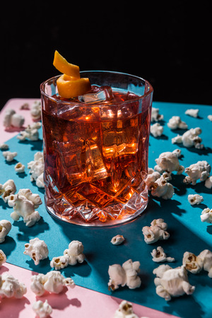Negroni IBA cocktail, with gin, bitter, vermouth, in pop contemporary style, colorful, dark background.