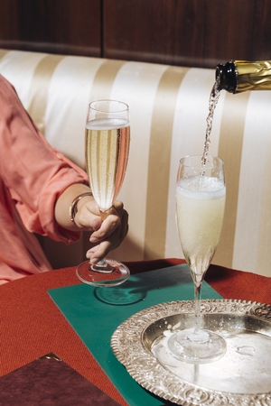 A glass of Prosecco held by a young woman in an elegant bar with vintage pop colors