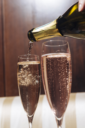 Filling flutes with Prosecco, italian white sparkling wine