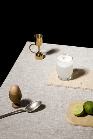 Pisco Sour, cocktail with Pisco, lime or lemon juice, egg white, and angostura bitter. Dark background, pop contemporary style.