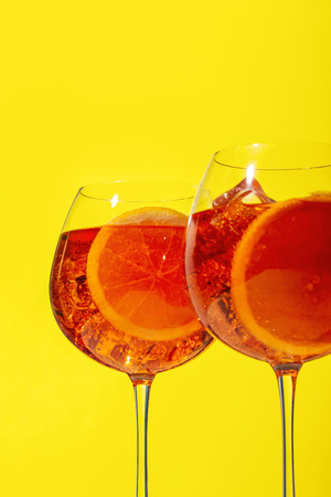 Spritz, a cocktail with sparkling Prosecco, bitter, seltz and orange slice, on yellow background