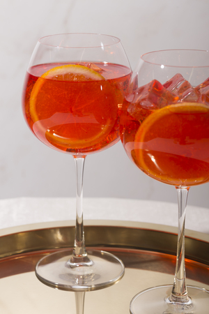 Spritz veneziano, an aperitif cocktail, with Prosecco or white sparkling wine, bitter, soda, ice and a slice of orange, in a calix on a table