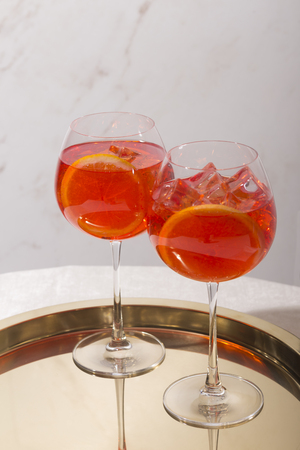 Spritz veneziano, an aperitif cocktail with Prosecco or white sparkling wine, bitter, soda, ice and a slice of orange, in a calix on a table