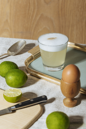 Pisco Sour, cocktail with Pisco, lime or lemon juice, egg white, and angostura bitter. Light background, pop contemporary style.