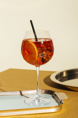 Spritz veneziano, an international italian cocktail with Prosecco or white sparkling wine, bitter, soda, ice and a slice of orange, in a calix on a table, pop graphic style
