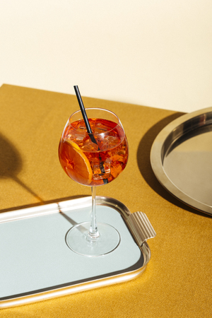 Spritz veneziano, an aperitif cocktail with Prosecco or white sparkling wine, bitter, soda, ice and a slice of orange, in a calix on a table, pop graphic style