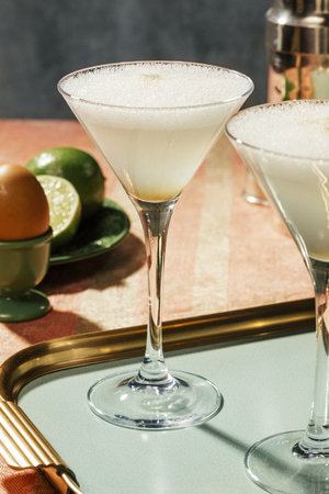Pisco Sour, a cocktail with Pisco, lime or lemon juice, egg white, and amargo chungo or angostura, in luxury contemporary style.