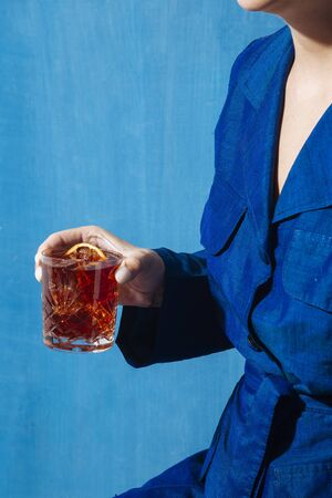 Woman and Negroni cocktail, with gin, bitter and vermouth. Colorful and trendy.