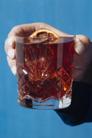 Womans hand and Negroni cocktail, with gin, bitter and vermouth. Colorful and trendy.