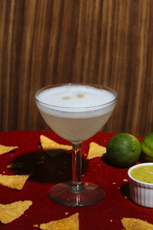 Pisco Sour, a cocktail with Pisco, lime or lemon juice, egg white, and angostura bitter. With nachos and guacamole Stock fotó
