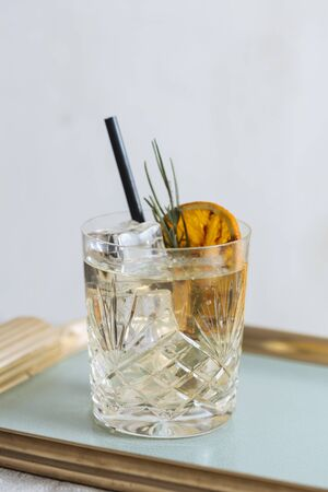 Gin and tonic garnished with charred orange and lavender, on an elegant tray