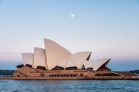 A bright full moon rising behind Sydney Opera House at dusk, while the sky shows a palette of pastel colours Редакционное