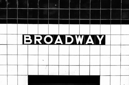 Broadway subway stop sign made of tiles opposite the platform