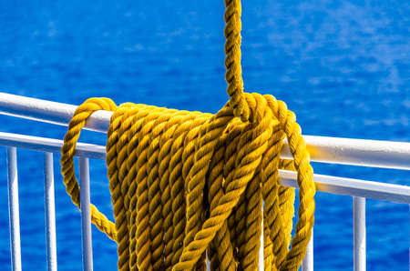 Close up of yellow braided rope draped over a ship railing