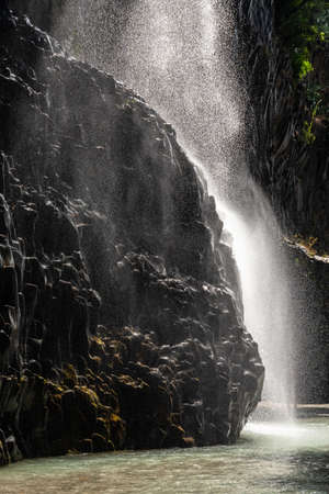View of basalt rocks, waterfalls and pristine water of Alcantara gorges in Sicily, Italy