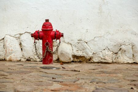 An old red fire hydrant in a stone paved street of the colonial town of Villa de Leyva, in the Andean mountains of central Colombia.