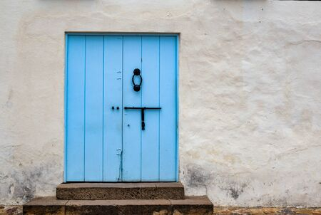 Blassblaue alte Tür in einer Straße der Kolonialstadt Villa de Leyva, in den Anden in Zentralkolumbien.