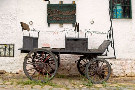 A very old carriage parked at an old stone paved street of the colonial town of Villa de Leyva, in the Andean mountains of central Colombia. The singboard reads: