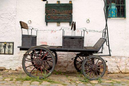 """Une très vieille voiture garée dans une vieille rue pavée de la ville coloniale de Villa de Leyva, dans les montagnes andines du centre de la Colombie. Le singboard se lit comme suit : """"Chevaux à louer"""", en espagnol. Banque d'images"""
