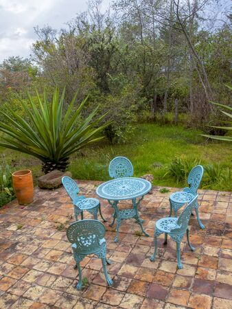 A metalic garden furniture on a clay tile terrace in a garden. At the Andean mountains of central Colombia.