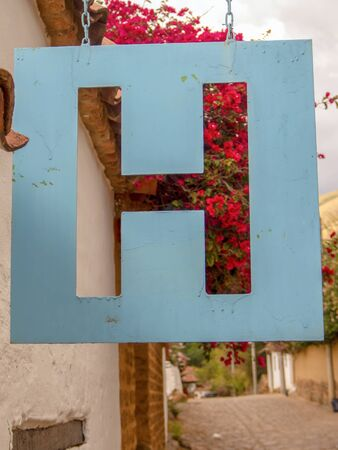 Close-up photography of a hanging metallic hotel signal. Photographed at a street of the colonial town of Villa de Leyva, in the central Andean mountains of Colombia.