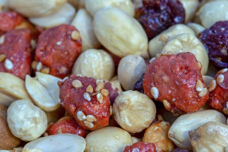 Macro photography of a heap of mixed nuts and cranberries.