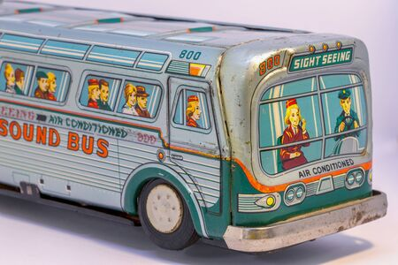Close-up photography of the front of a rusty vintage tin bus toy.