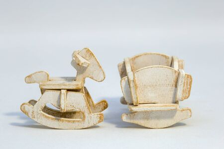 Macro photography of an assembled wooden rocking horse and a cradle miniature toys.