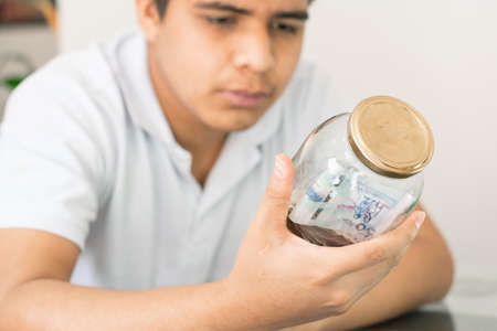 serious guy with glass jar full of banknotes in hand. young man collecting personal finances from him. thrifty boy. savings and finance concept. man looking at his savings Standard-Bild