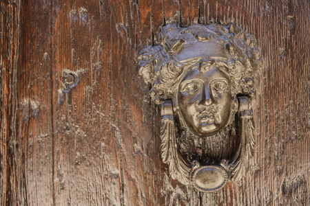 Door knocker in the form of a girl's head with grape leaves on a wooden door