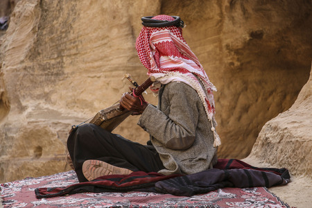 Old bedouin in the keffiyeh plays on the national musical instrument of Jordan,Petra, Jordan