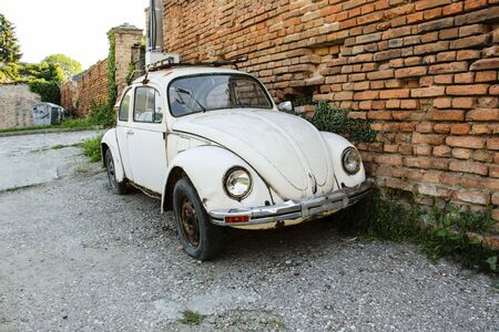 BELGRADE, SERBIA- JUNE 07, 2019: White Volkswagen Beetle retro car parked near a brick wall at the city street Belgrade, Serbia.