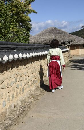 Woman in a traditional Korean costume in the street Andong Hahoe Folk Village in Andong, South Korea.