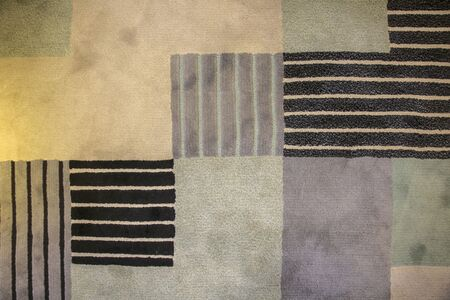 Texture of textile rug with pattern of beige, gray and black colors