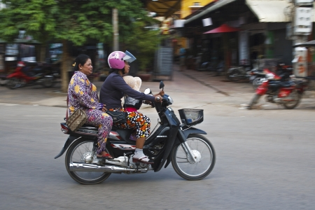 Siem Reap, Cambodia - April 21, 2013: A young child holds on by a woman while riding a scooter on the streets of Siem Reap, Cambodia Stock Photo - 19416098