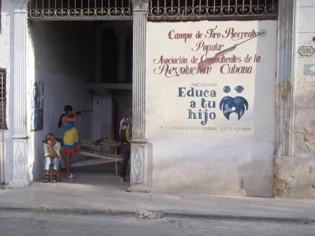 bb gun: Havana, Cuba - April 24, 2012: A  woman shooting at a bb gun shooting gallery open to the street. Editorial