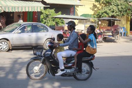Siem Reap, Kambodscha - 1. Mai 2013: vier Personen einen Motorroller fahren auf den Straßen von Siem Reap, Kambodscha. Dieses Land ist sehr arm und Roller ist ein weit verbreitetes Verkehrsmittel
