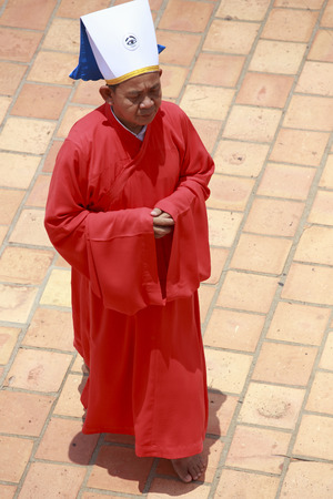 taoisme: Tay Ninh, Vietnam - 22 april 2014: rode priester in een Caodai tempel in Vietnam. Caodai is een Vietnamese religie mengen van verschillende religies uit de hele wereld, waaronder het boeddhisme, het confucianisme, christendom, hindoeïsme, islam, jodendom, taoïsme en Geniism.