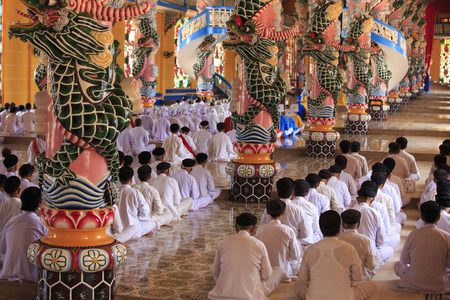 tay: Tay Ninh, Vietnam - April 22, 2014: People praying in a Caodai temple in Vietnam. Caodai is a Vietnamese religion mixing different religions from around the world, including Buddhism, Confucianism, Christianity, Hinduism, Islam, Judaism, Taoism, and Genii