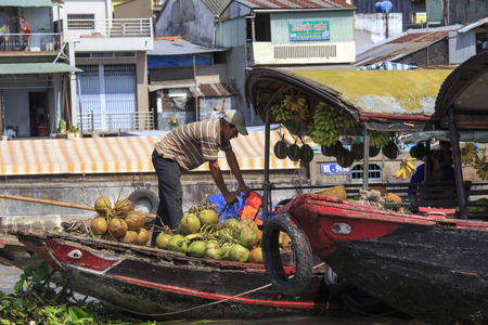 Cai Be, Vietnam - April 23, 2014: Traders on boats navigate in early morning light in Mekong Delta region of Vietnam. Cai Be is famous for its busy floating market.