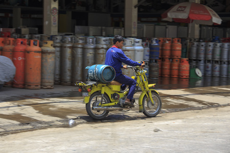 cilinder: Phnom Phen, Cambogia - 25 aprile 2014: gli uomini non identificati sta trasportando cilindro del gas in moto
