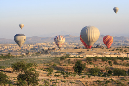 """ascends: Cappadocia, Turkey,€"""" August, 12 2014 : Early morning in Cappadocia, Turkey, dozens of hot air balloons offer guests from all over the world spectacular and breathtaking views of the Cappadocian lunar like landscape. Experienced balloon pilots ascends a"""