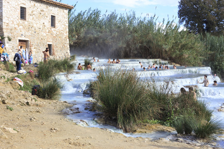 etruscan: Saturnia, Italy - November 17, 2013: Locals and tourists swim in the famous hot springs in Saturnia. Saturnia is a spa town in the municipality in Manciano in the Tuscan Maremma, Italy. Bathing in the natural pools created sintering is free. Editorial