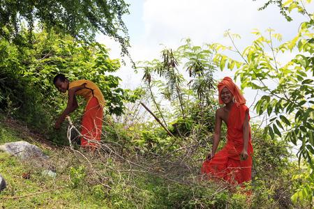 penh: PHNOM PENH, CAMBODIA - APRIL 25, 2014 - Young Buddhist monks in a garden collecting plants, Phnom Penh, Cambodia