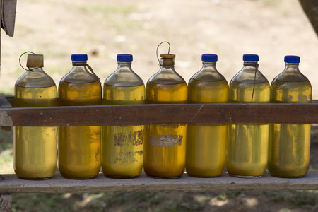 vendor: Gasoline for motorbikes sold from whisky bottles by a roadside vendor Stock Photo