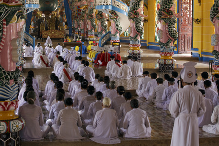taoism: Tay Ninh, Vietnam - April 22, 2014: People praying in a Caodai temple in Vietnam. Caodai is a Vietnamese religion mixing different religions from around the world, including Buddhism, Confucianism, Christianity, Hinduism, Islam, Judaism, Taoism, and Genii