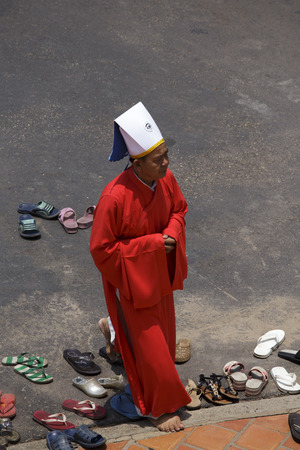 judaism: Tay Ninh, Vietnam - April 22, 2014: Priest going in a Caodai temple in Vietnam. Caodai is a Vietnamese religion mixing different religions from around the world, including Buddhism, Confucianism, Christianity, Hinduism, Islam, Judaism, Taoism, and Geniism Editorial
